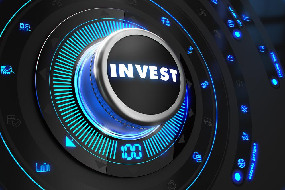 Invest Regulator on Black Control Console with Blue Backlight. Improvement, regulation, control or management concept.